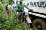 Bibo, the 34-year Habal-habal driver, keeps his balance on this bike as he drives through a narrow passage when a dump truck was stuck on its way up near Sitio Diat 2, Barangay Napnapan, Pantukan, Compostela Valley on January 6. The dump truck, which was carrying food supplies for the rescue volunteers, could no longer climb due to steep and slippery road. Keith Bacongco