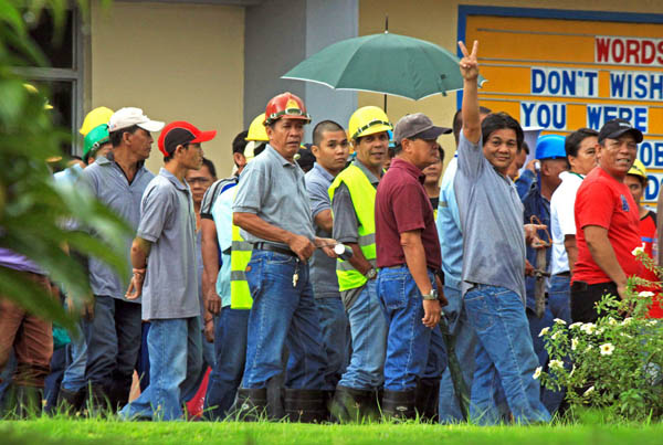 NOISE BARRAGE. A worker flashes a V sign as he joins co-workers in staging a noise barrage in front of the administration office of the Pacific Cement Philippines Inc., in Kilomter 11, Surigao City . January 12, to urge management to release benefits due them. MindaNews photo by Roel N. Catoto
