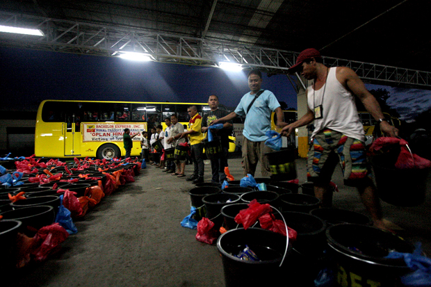 Workers of Bachelor Express and Rural Transit Mindanao bus lines load relief goods onto a bus on Monday night, December 17 at their headquarters in Maa, Davao City. The relief goods--consisting of pails, noodles, sardines, medicines and rice--will be delivered today, December 18 to typhoon stricken areas in Compostela Valley and Davao Oriental Provinces. MindaNews Photo by Ruby Thursday More