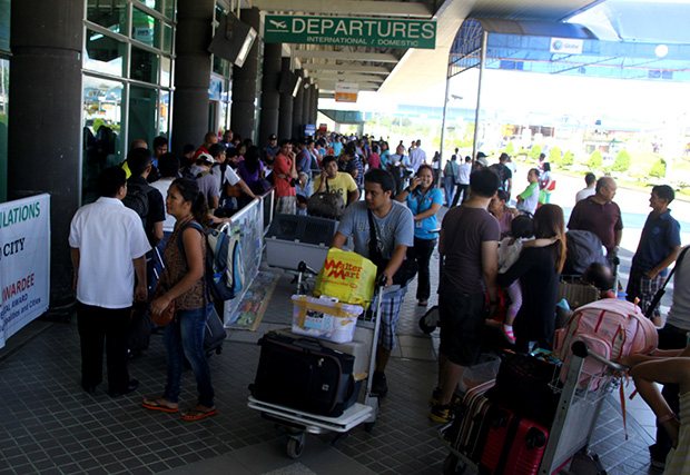 Passengers mill outside the departure area of the Francisco Bangoy International Airport in Davao City Monday morning (3 June 2013). The DOTC reported that at least 10 flights to Davao City have already been cancelled as the Cebu Pacific flight 5J 971 that overshot the runway the night before is still stuck on runway as of Monday morning. Mindanews Photo by Keith Bacongco