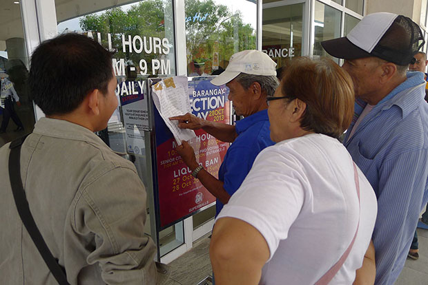 Senior citizens look for their names at the entrance of SM City General Santos during the special voting for senior citizens and persons with disabilities on Monday's (October 28) barangay polls. (Bong S. Sarmiento/MindaNews)