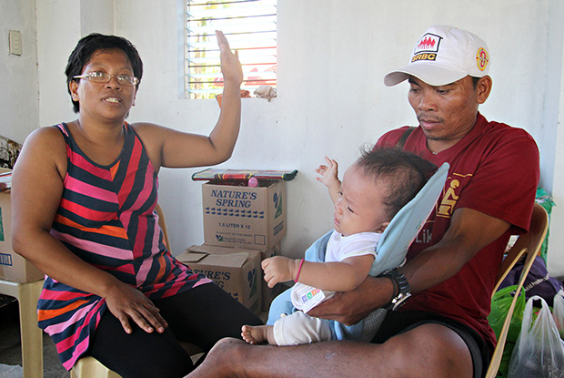 Josie Togonon describes how the storm surge caused by super typhoon Yolanda killed hundreds of people in their community in Old Road Sagkahan in Tacloban City. Josie's husband Ronnel (right) holds their 3-month old baby girl who almost fell into the water while they were trying to flee the fast rising waters. MindaNews photo by Erwin Mascarinas