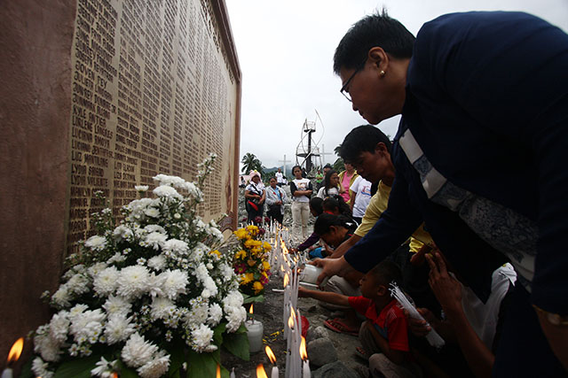 elatives of victims of Typhoon Pablo offer flowers at the marker that carries the name of those who died and those who are still missing. About 2,000 people came for the commemorative mass held at the San Roque chapel in Barangay Andap, New Bataan, Compostela Valley on Wednesday, 4 December 2013. MindaNews photo by Ruby Thursday More