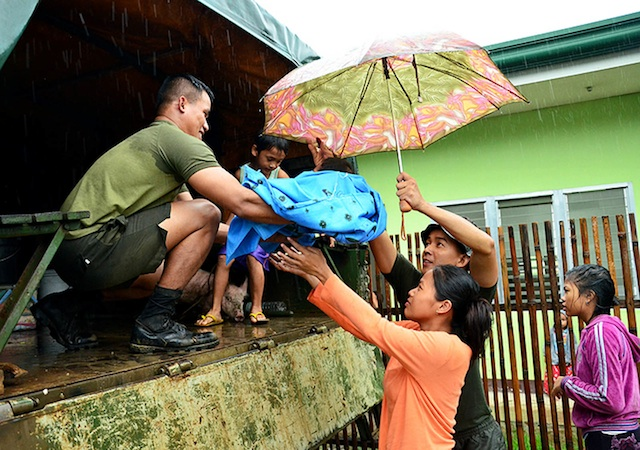 "EVACUATION.  A couple hands over their baby to a soldier before boarding an Army truck  in Barangay Cala-anan, Cagayan de Oro City on Jan. 20. Rains brought by  tropical depression ""Agaton""  triggered floods in the city and Misamis Oriental province. Photo courtesy ofr Cagayan de Oro Information Office/ Rhoel Condeza"