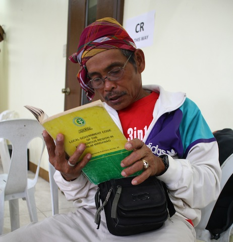 Timuay Rodrigo Mokudef, a bliyan (priest-healer), reads portions of the Local Governments Act of the Autonomous Region in Muslim Mindanao, one of the books on display  at the 1st Mindanao Book Festival in Cotabato CIty. MindaNews photo by Greogrio Bueno