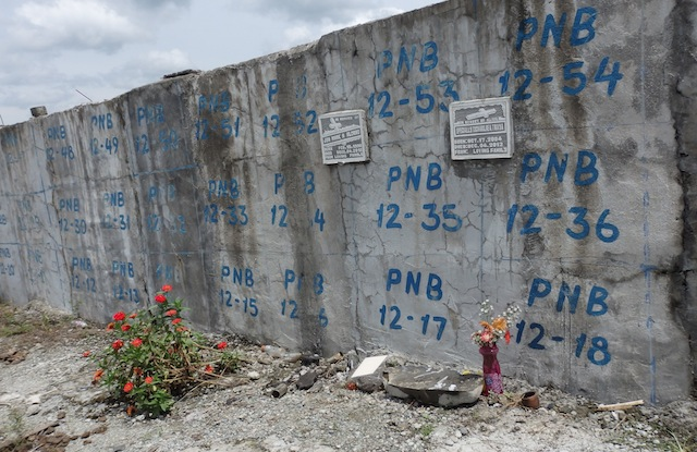 CAN'T WAIT. Relatives of Jun Mark Alcano, 12 and Charlie Traya, 8, no longer waited for the National Bureau of Investigation – Disaster Victim Identification (NBI-DVI) to release the results of the DNA matching. Before November 1, 2013, they claimed a space in the burial vault at the public cemetery in New Bataan, Compostela Valley, and there attached their lapida (grave marker). MindaNews photo by Carolyn O. Arguillas