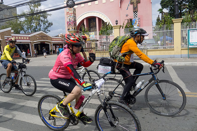 Fr. Picx and biking buddies from the Naawan Bikers (NAB) and the Unified Cycling Clubs of Iligan (UCCI) pass by the St. Michael's Cathedral in downtown Iligan. MindaNews photo by Bobby Timonera