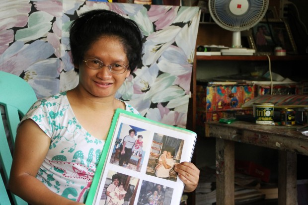 Bagani de los Santos shows photos of her younger years and art works at their home in Ampayon, Butuan City. Bagani was born with many disabilities but shows innate talent in art. MindaNews photo by H. Marcos C. Mordeno