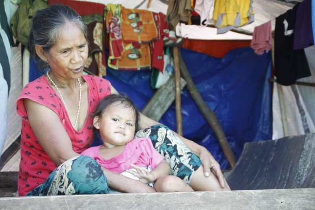 Erlinda Pagalan, a bakwit from Sitio Han-ayan, Barangay Diatagon in Lianga, Surigao del Sur share with a grandchild a small space at the evacuation site in Tandag City on Thursday (1 October 2015). MindaNews photo by H. Marcos C. Mordeno