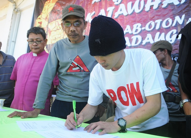 20soldier2 FREED. After 133 days in captivity, Army PFC. Adonis Jess Lupiba (in white shirt) signs his release papers from his NPA captors in barangay Kaulayanan, Sugbongcogon town in Misamis Oriental on Nov. 20, 2015. Lupiba was captured by the rebels after a brief firefight in Barangay Alagatan, Gingoog City last July 11, 2015. MindaNews photo by Froilan Gallardo