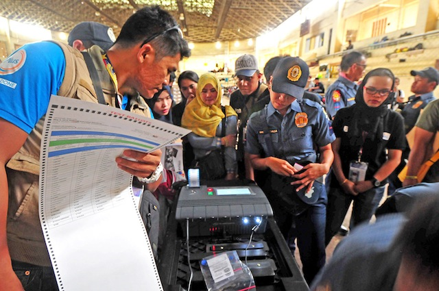 FINAL TESTING. A technician from Smartmatic checks the Vote Counting Machine (VCM) together with policemen and poll watchers at the Lanao del Sur provincial gym in Marawi City, on Sunday, May 8, 2016. Some 200 policemen will take up poll duties to replace teachers who expressed fear of violence during the election on Monday. MindaNews photo by FROILAN GALLARDO