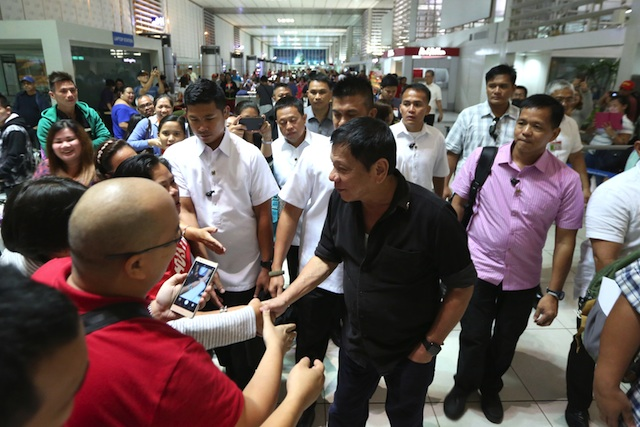 President Rodrigo Duterte greets surprised airline passengers at the Ninoy Aquino International Airport II where he boarded a commercial flight from Manila to Davao at 9 p.m. on Thursday, July 7. KING RODRIGUEZ / Presidential Photographers Division